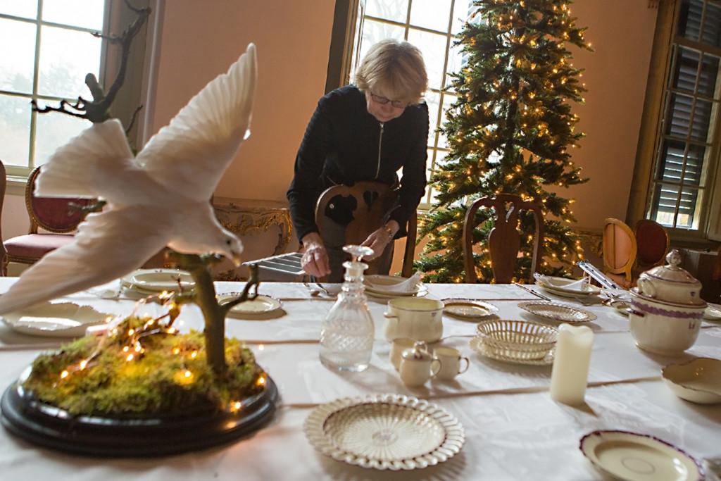 """De vrijwillgers van kasteel Amerongen zijn maandag van start gegaan om het kasteel Amerongen in kerstsfeer te brengen. vanaf 19 december gaat """" Kerst op kasteel van Amerongen"""" van start. Van 19 december tot en met 3 januari is Kasteel Amerongen ondergedompeld in een romantische kerstsfeer.Met dit jaar als thema 'Oh dennenboom, wat ben je mooi!' vindt u door het hele Huys heen speciaal opgetuigde kerstbomen. Er is toegang tot diverse kamers die anders gesloten blijven zoals wijnkelder, Engelenkamer en jachtkelder. Op de bel-etage komt, behalve in de eetzaal, ook in de salon een schitterend gedekte kersttafel met bijpassende boom. En dit jaar mag u de in oude glorie herstelde gobelinkamer natuurlijk niet missen. Op verschillende dagen is er live muziek in het Huys te horen. Op de foto: Marja Heethaar bezig met het dekken van de eettafel"""