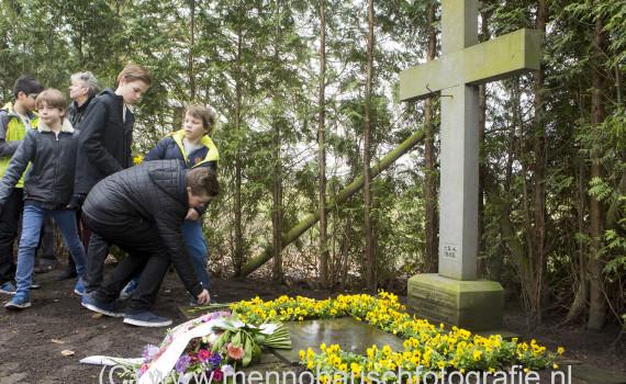 Kinderen leggen bloemen bij oorlogsmonument